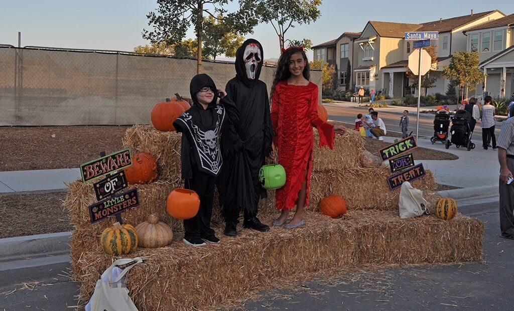 Kids posing in costumes with haystacks and pumpkins
